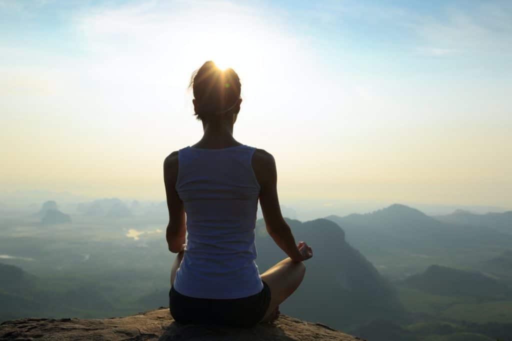Meditation on sunrise mountain top cliff edge