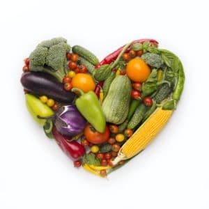 Heart shape frame of fresh vegetables on white background